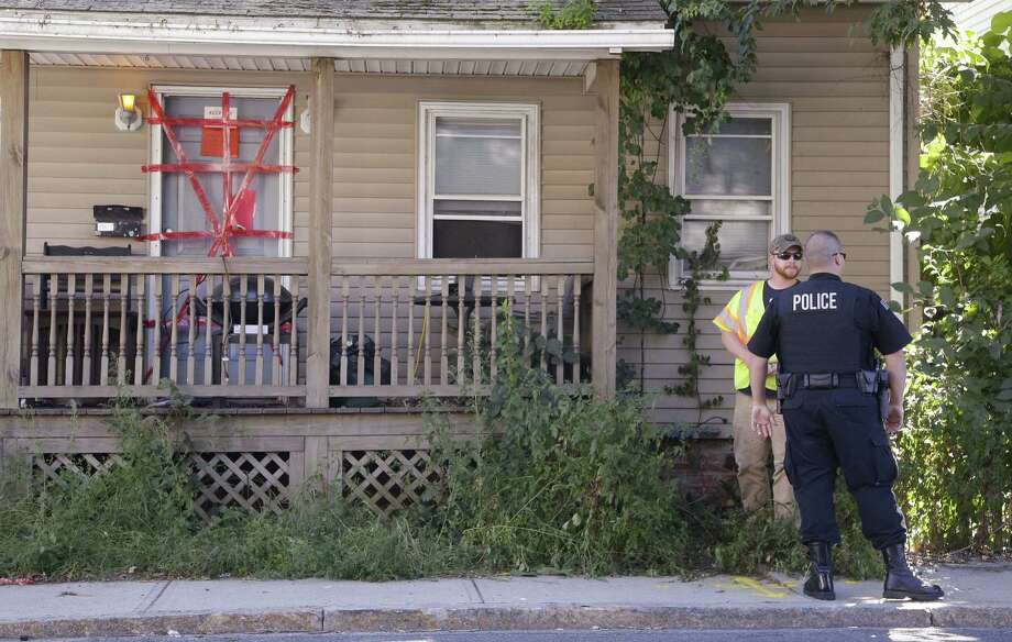 """A Blackstone police officer talks with a utility worker while standing outside a house where a Massachusetts prosecutor said the bodies of three infants were found Thursday.  """"Condemned"""" and """"Keep out"""" signs are attached to the front door. Photo: Associated Press / AP"""