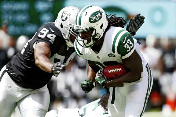 In his debut with the Raiders on Sunday, Antonio Smith, left, created a roadblock for the Jets' Chris Ivory. He looks forward to seeing his old Texans pals.