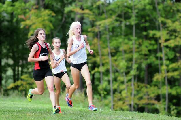 Guilderland's Emily Burns, left, who came in first, rounds a corner with Saratoga Springs' Paris Fenoff, center, and Peyton Engborg during the varsity girls Springstead Invitational Cross Country Meet on Friday, Sept. 12, 2014, at Colonie Town Park in Colonie, N.Y. (Cindy Schultz / Times Union) Photo: Cindy Schultz / 00028531A