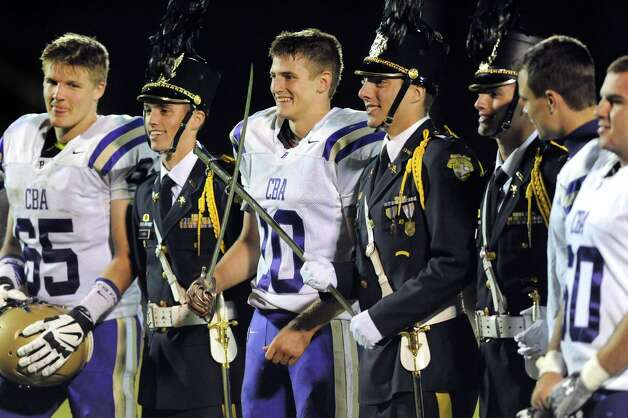 """CBA's Donald Vivian, center, poses with the saber after his team wins the """"Game for the Sabre"""" in their football game against La Salle on Friday, Sept. 12, 2014, at La Salle Institute in Troy, N.Y. (Cindy Schultz / Times Union) Photo: Cindy Schultz / 00028564A"""