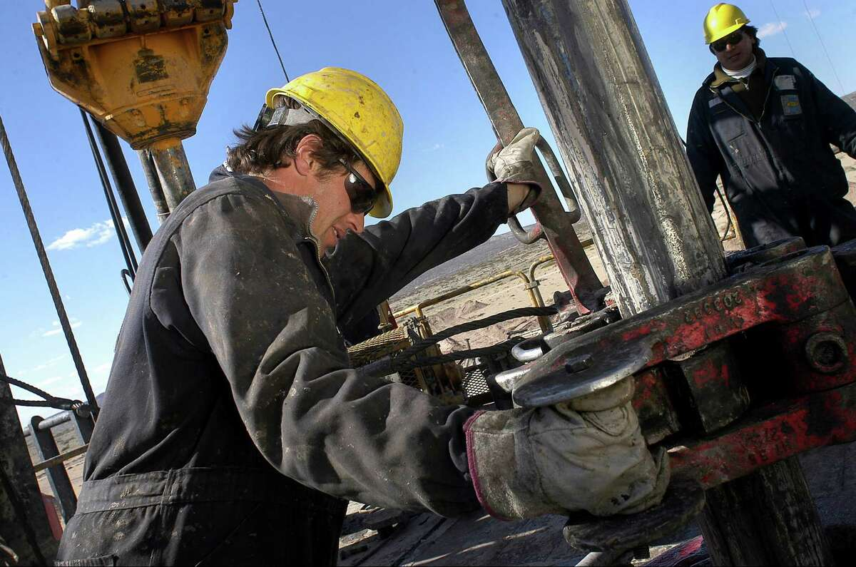 In this picture taken Nov. 24, 2009, an oil worker works on an oil drill in the province of Neuquen, Argentina. Argentina is promoting a new era of mining and energy production, welcoming billions of dollars in foreign investment to unlock huge new reserves of natural gas, oil, gold, lithium and other metals once thought to be unprofitable or out of reach. But there's one factor threatening this resource boom, something politicians and energy executives rarely mention: Huge amounts of fresh water will be required to extract these resources, in a country where water scarcity has long held back development and 16 percent of households still aren't connected to publicly treated drinking water. (AP Photo/Leonardo Petricio)