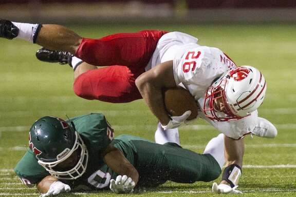 Katy Tiger Rodney Anderson is tripped up by  Woodlands Highlander Antoine Winfield during the second half of a football game at Woodforest Bank Stadium, Friday, Sept. 12, 2014, in Shenandoah. The Highlanders won 24-7. (Cody Duty / Houston Chronicle)