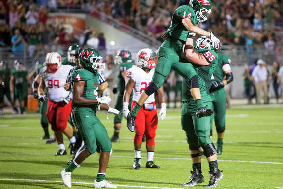 Teammates celebrate Woodlands Highlander Hunter Moore after he scored a touchdown during the first half of a football game against the The Katy Tigers, at Woodforest Bank Stadium, Friday, Sept. 12, 2014, in Shenandoah. (Cody Duty / Houston Chronicle)