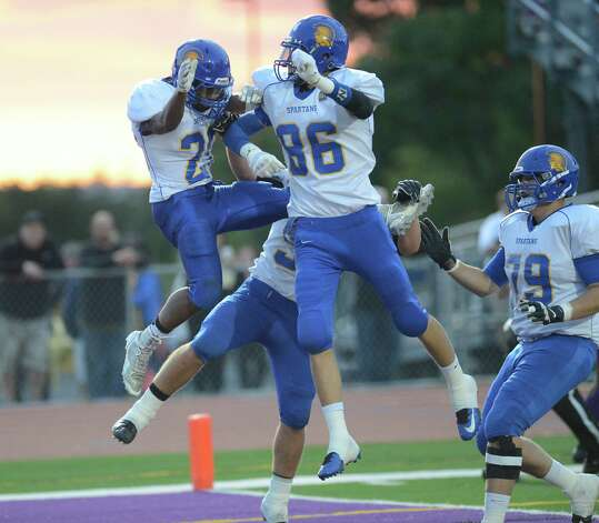Queensbury's Tyrell Adams (20) left celebrates a touchdown with teammates after scoring against Troy during the first half of their Section II Class A football game on Friday, Sept. 12, 2014, in Troy , N.Y., (Hans Pennink / Special to the Times Union) ORG XMIT: HP106 Photo: Hans Pennink / Hans Pennink