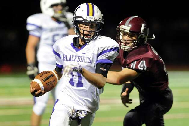 Voorheesville's quarterback Robert Denman, center, carries the ball as Watervliet's Collin O'Brien defends during their football game on Friday, Sept. 12, 2014, at Watervliet High in Watervliet, N.Y. (Cindy Schultz / Times Union) Photo: Cindy Schultz / 00028563A