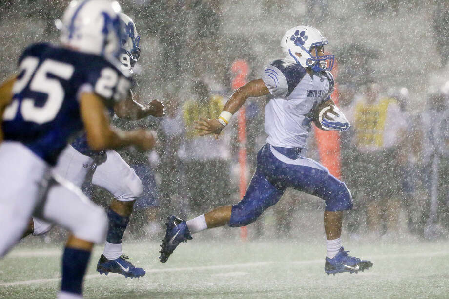 South San's William Sanchez (right) picks up yardage in the rain during the second quarter of their game with MacArthur at Comalander Stadium  on Friday, Sept. 12, 2014.  MacArthur beat the Bobcats 42-14.  MARVIN PFEIFFER/ mpfeiffer@express-news.net Photo: MARVIN PFEIFFER, MARVIN PFEIFFER/ Mpfeiffer@express-news.net / Express-News 2014
