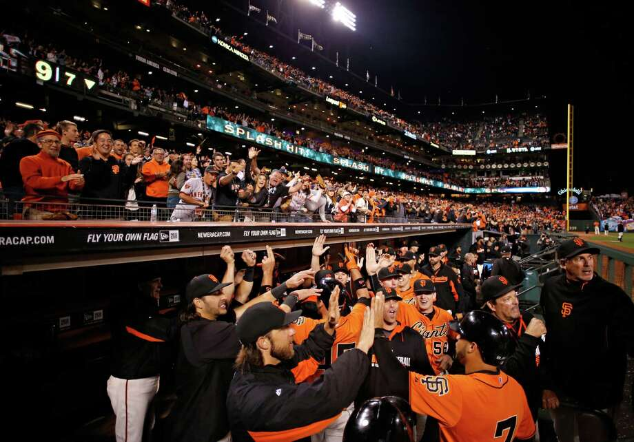 San Francisco Giants' Gregor Blanco, Brandon Crawford and Travis Ishikawa are welcomed back to the dugout after all three scored on a three run homerun by Ishikawa during the seventh inning of his baseball game against the Los Angeles Dodgers on Friday, September 12, 2014 in San Francisco, Calif. Photo: Beck Diefenbach, Contributor / Special To The Chronicle / ONLINE_YES