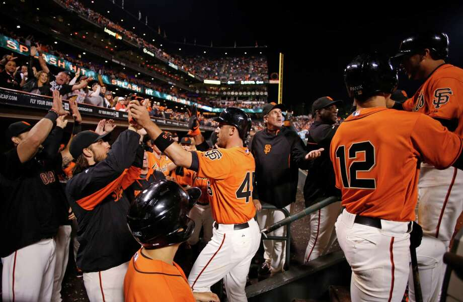 Travis Ishikawa (center), being greeted after a September home run, was drafted and developed by the Giants before leaving as a free agent and then returning. Photo: Beck Diefenbach / Special To The Chronicle / ONLINE_YES