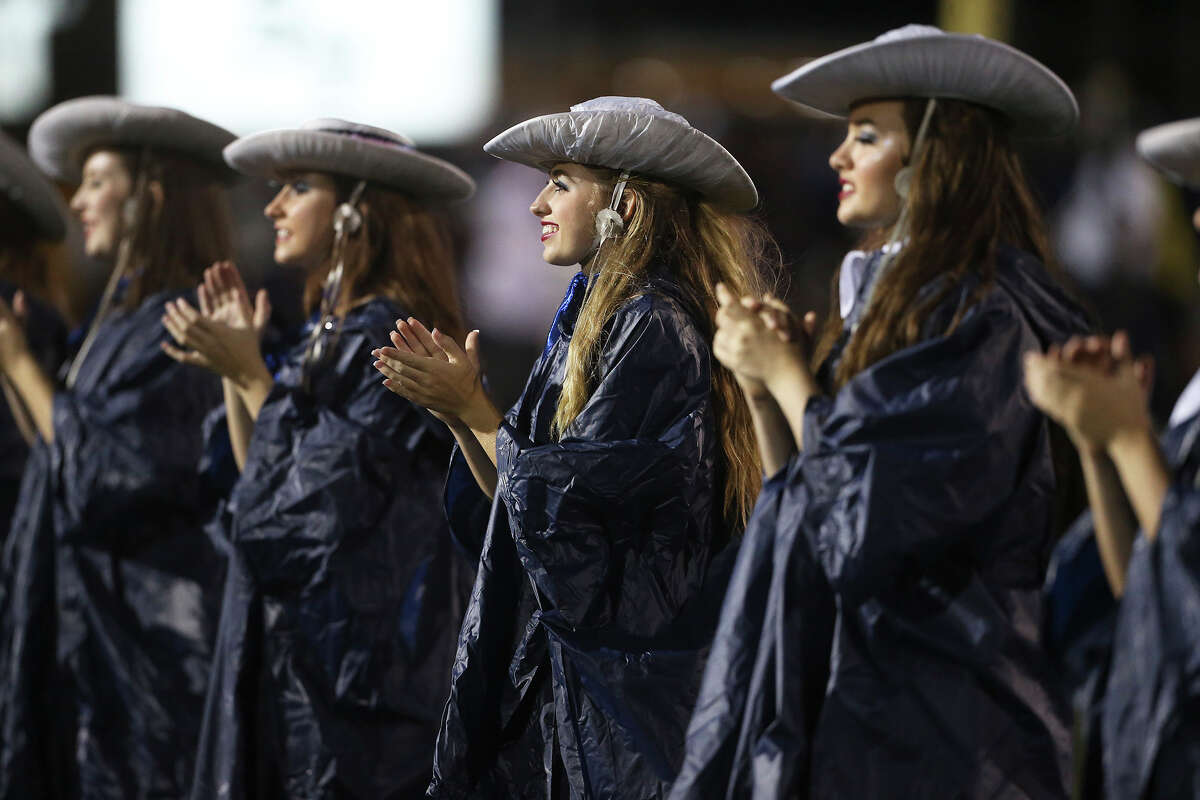 Dancers for the Rangers stand in drizzle pre game as Smithson Valley hosts East Central at Ranger Stadium on September 12, 2014.