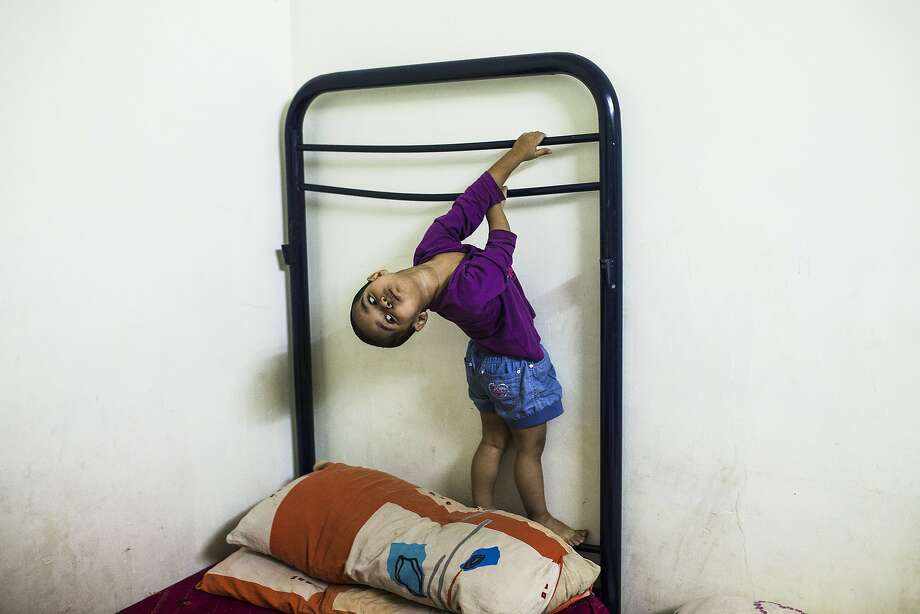 EDS NOTE - SPANISH LAW REQUIRES THAT THE FACES OF MINORS ARE MASKED IN PUBLICATIONS WITHIN SPAIN Fabha, 2 years-old, and Oliur Rahman's daughter, plays holding herself from a disassembled bed as she waits to get evicted in Madrid, Spain, Friday, Sept. 12, 2014. The landlord's loss of the apartment to a  bank is causing Rahman family's eviction. Oliur Rahman and his wife Hamida and their two children of 2 and 6 years old moved into the foreclosed apartment paying a rent of 300 euros ($388) a month. With a monthly pay-check of only euros 700 a month ($ 907) this was his only option. The eviction was finally postponed with the help of the housing rights activists. (AP Photo/Andres Kudacki) Photo: Andres Kudacki, Associated Press