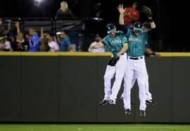 Seattle Mariners outfielders, from left, Chris Denorfia, Michael Saunders, and Austin Jackson leap after the Mariners defeated the Oakland Athletics 4-2 in a baseball game, Friday, Sept. 12, 2014, in Seattle. (AP Photo/Ted S. Warren)