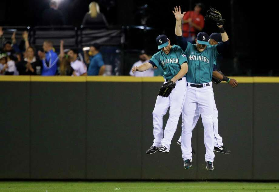 Seattle Mariners outfielders, from left, Chris Denorfia, Michael Saunders, and Austin Jackson leap after the Mariners defeated the Oakland Athletics 4-2 in a baseball game, Friday, Sept. 12, 2014, in Seattle. (AP Photo/Ted S. Warren) Photo: Ted S. Warren, STF / Associated Press / AP
