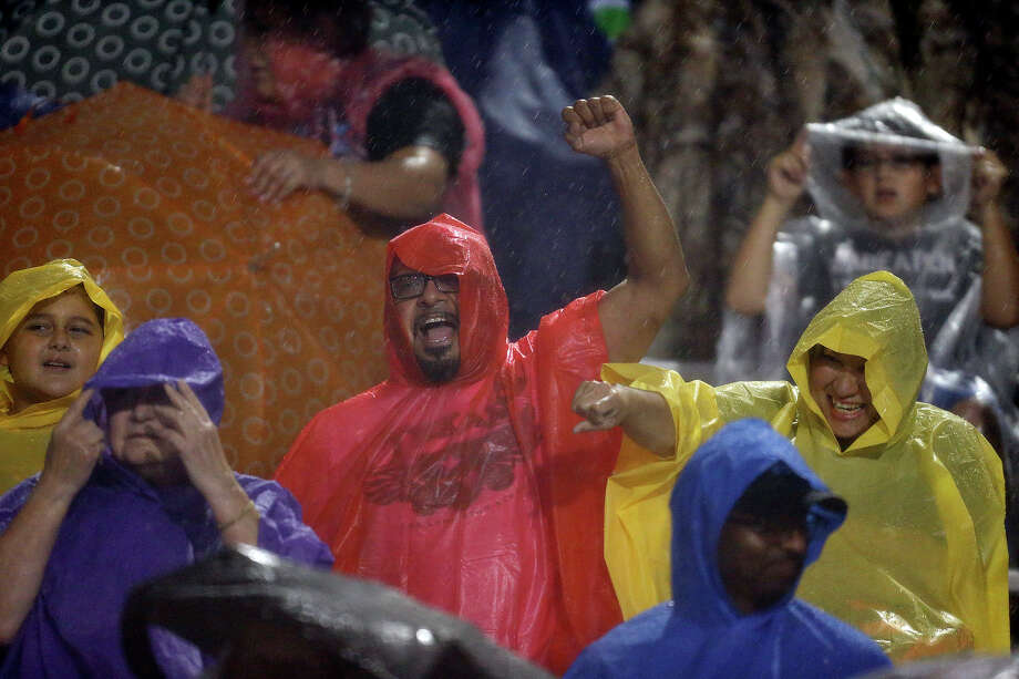 Football fans cheer in the rain during the Steele and O'Connor game Friday Sept. 12, 2014 at Lehnhoff Stadium. Photo: Edward A. Ornelas, By Edward A.Ornelas/Express-News / © 2014 San Antonio Express-News