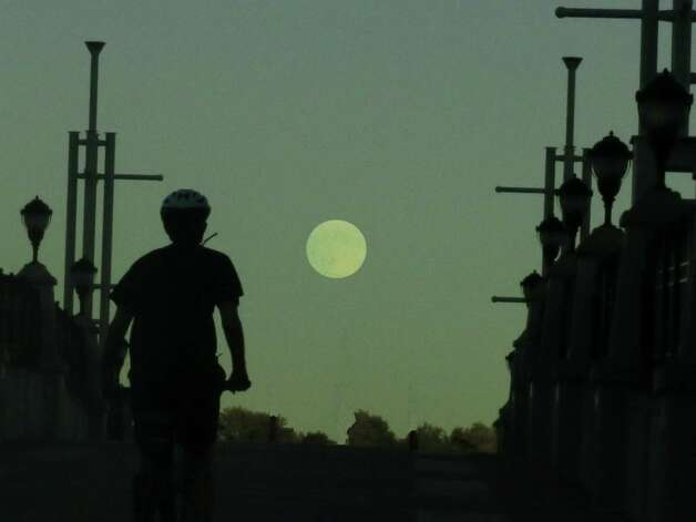 Bicyclist near Jennings' Landing in Albany riding towards the rising harvest moon. (Richard Shore) Photo: Richard Shore / (c) 2014 richard shore
