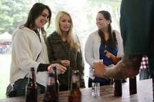 Stevie Sacco, left, Amanda Holovac, center, and Erin Sawyer, of Southbury, sample Sam Adams Octoberfest, poured by event volunteer Andrew Middlebrook during Connecticut on Tap at Ives Concert Park in Danbury, Conn. Saturday, Sept. 13, 2014.  Hundreds huddled under tents in the rain to take part in the beer-tasting event featuring more than 120 American craft breweries.