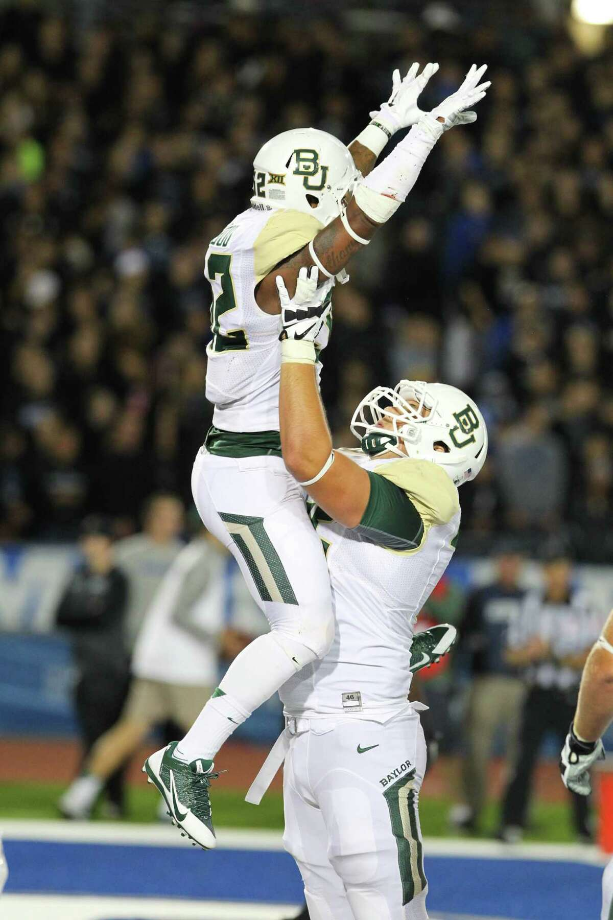 Baylor running back Shock Linwood (32) celebrates his touchdown with tackle Troy Baker (75) during the first half of an NCAA college football game against Buffalo on Friday, Sept. 12, 2014, in Amherst, N.Y.