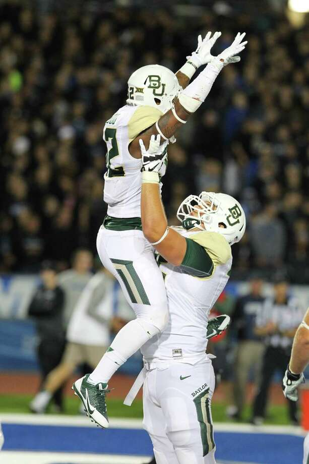 Baylor running back Shock Linwood (32) celebrates his touchdown with tackle Troy Baker (75) during the first half of an NCAA college football game against Buffalo on Friday, Sept. 12, 2014, in Amherst, N.Y. Photo: Bill Wippert, AP / FR170745 AP