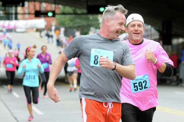 Friends Bill Bernosky, center, and John Docherty, both of Albany race to the finish line during the 20th annual Komen Northeastern New York Race for the Cure  on Saturday, Sept. 13, 2014, in Albany, N.Y. (Cindy Schultz / Times Union) Photo: Cindy Schultz / 00028603A