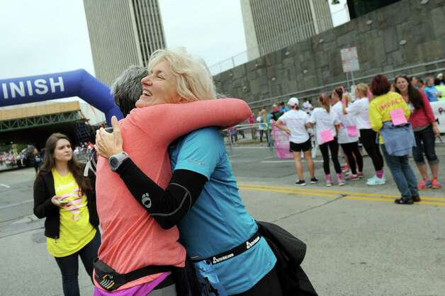 Glenda Cohen, right, embraces her sister Brenda Hacker of Loudonville, who's a breast cancer survivor, at the finish line of the 20th annual Komen Northeastern New York Race for the Cure  on Saturday, Sept. 13, 2014, in Albany, N.Y. (Cindy Schultz / Times Union) Photo: Cindy Schultz / 00028603A