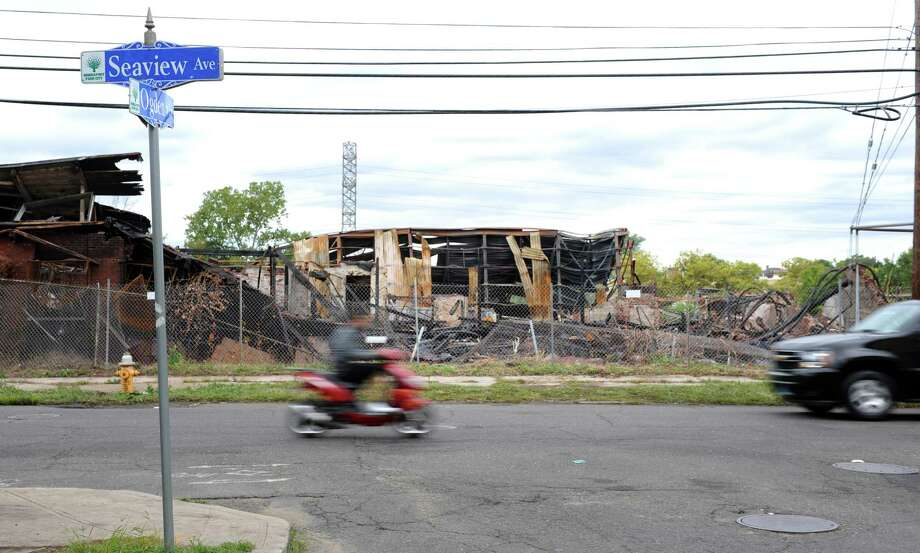 Vehicles move past the wreckage of a warehouse on Seaview Avenue Saturday, Sept. 13, 2014 following the Thursday night fire that destroyed the building. Photo: Autumn Driscoll / Connecticut Post