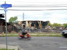 Vehicles move past the wreckage of a warehouse on Seaview Avenue Saturday, Sept. 13, 2014 following the Thursday night fire that destroyed the building.