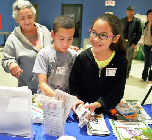 Carmen Felix, left, and her grandchildren Ivan Reyes, 9, and Kavina Roman,right, 11, all of Albany, at the United Health Community and State booth during SONYMA's Hispanic Heritage Celebration in the Empire State Plaza Convention Center Saturday Sept. 13, 2014, in Albany, NY.  (John Carl D'Annibale / Times Union) Photo: John Carl D'Annibale / 00028609A