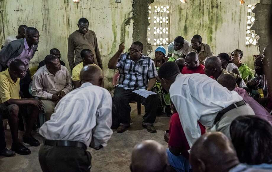 Dr. Mosoka Fallah (center) an epidemiologist and immunologist, talks with residents of New Kru Town, a district in Monrovia, Liberia, about stopping the spread of Ebola. Photo: New York Times / NYTNS