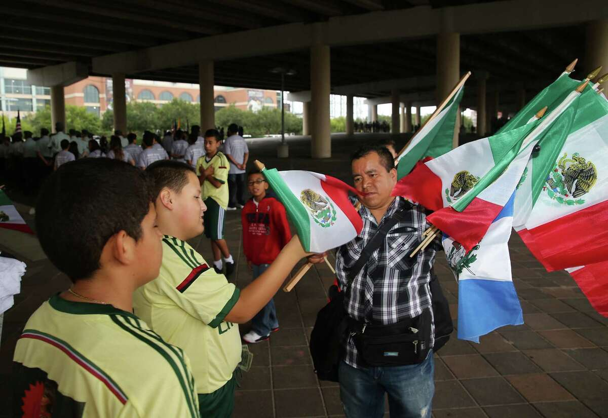Yajdiel Guevara buys a Mexican flag from Obispo Diego before the start of the 46th Annual Fiesta Patrias International Parade in downtown Houston, TX.