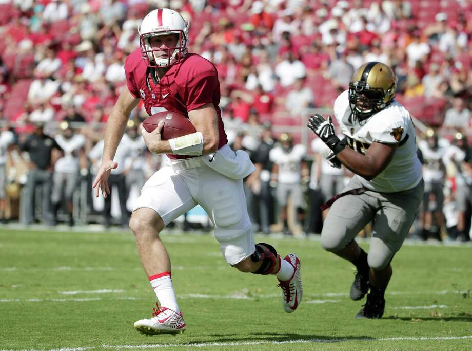 Stanford quarterback Kevin Hogan scampers away from Army defensive lineman Richard Glover during the first half of the Cardinal's victory. Hogan passed for 216 yards and four touchdowns as Stanford improved to 2-1. For details, see story on B7. Photo: Marcio Jose Sanchez, STF / Associated Press / AP