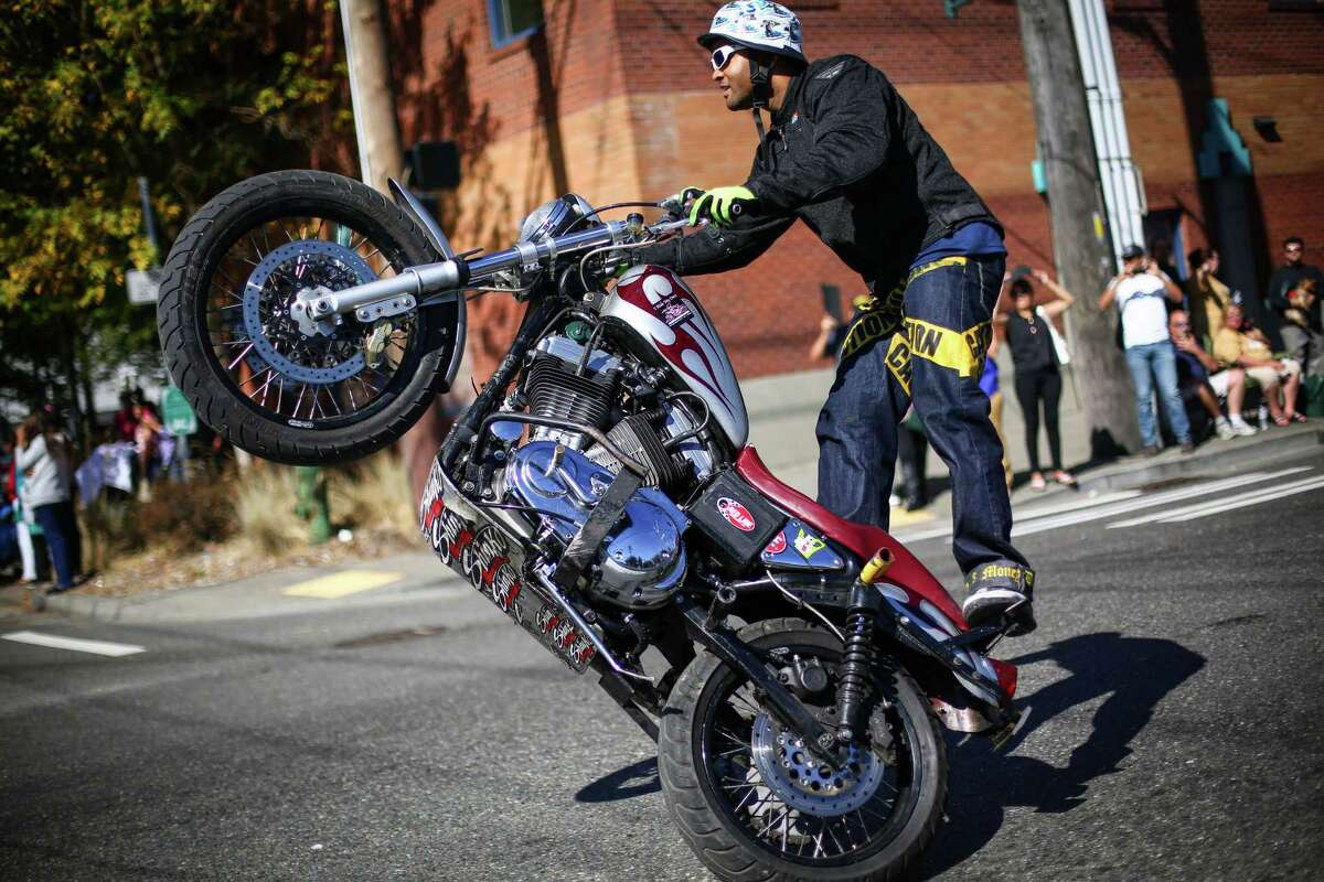 Hollywood B motorcycle stunt rider performs during the annual Fiestas Patrias Parade in Seattle's South Park neighborhood.