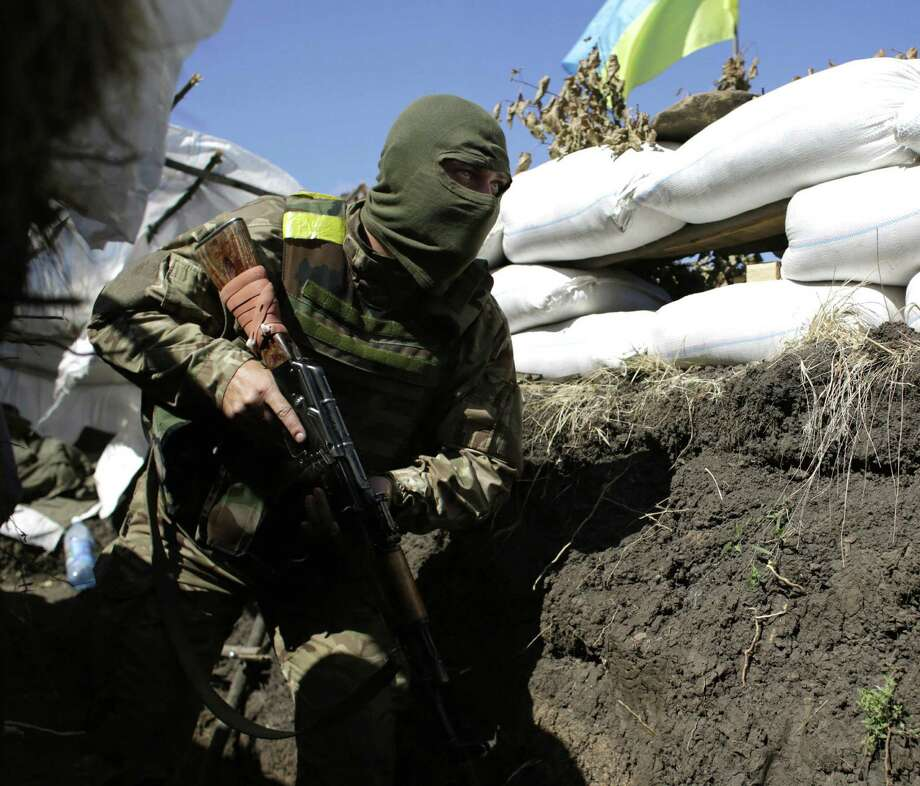 A Ukrainian soldier moves into position in a trench close to the small eastern Ukrainian city of Pervomaysk, in the Lugansk region. Photo: Anatolii Stepanov / Getty Images / AFP