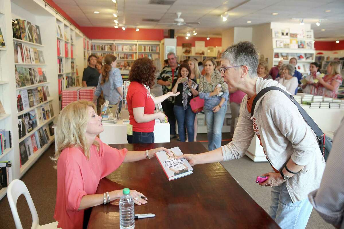 Gubernatorial candidate and state Sen. Wendy Davis signs a copy of her memoir for Jeanne Blanchard while on her book tour at Brazos Bookstore in Houston on Saturday.