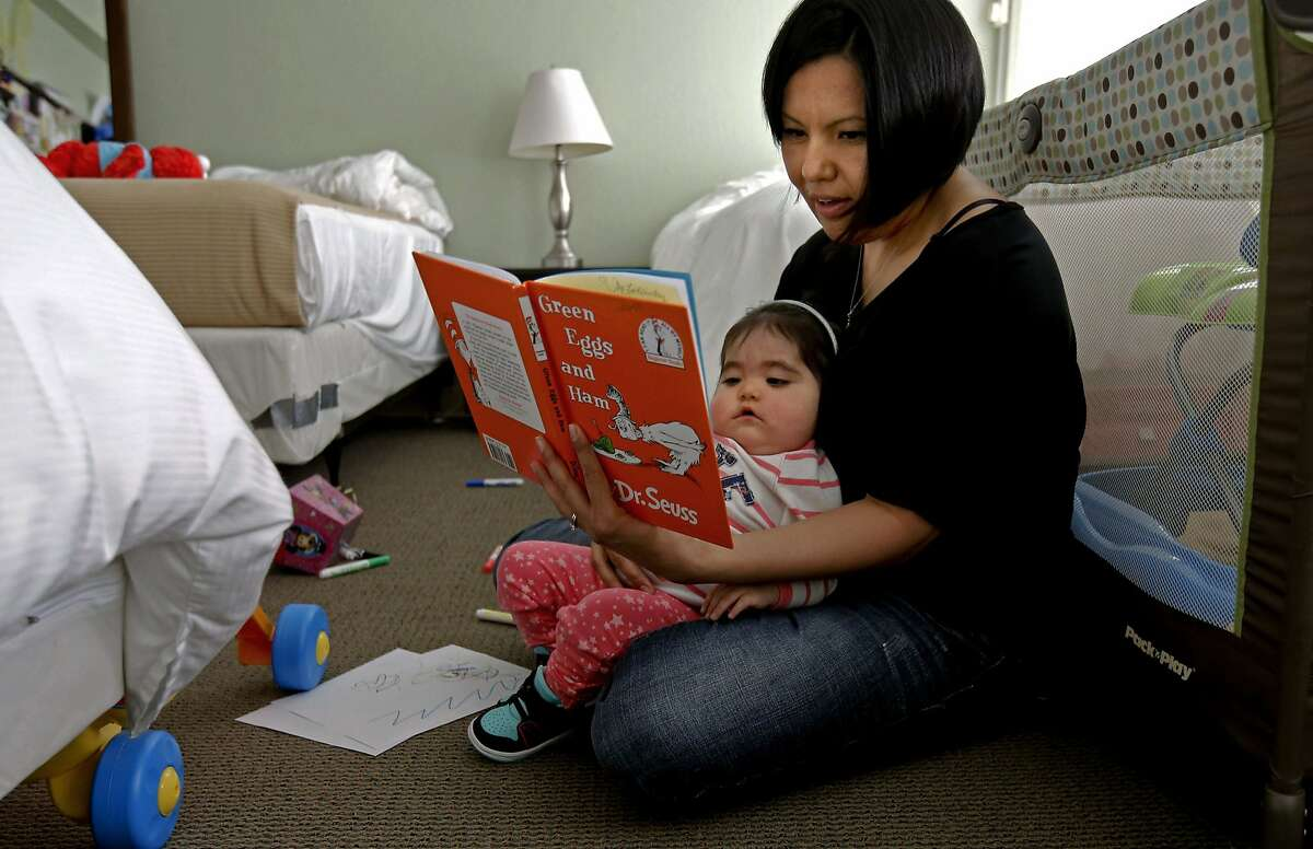 1-year-old Joy Littlesunday is read to by her mom Christina, inside their room where they have been staying since July 2013 at the Koret Family House in San Francisco, Calif., as seen on Tuesday Sept. 9, 2014. Joy has been receiving treatment for SCID (Severe Combined Immunodeficiency). Koret Family House provides. temporary housing to families of seriously ill children receiving treatment at the University of California San Francisco Benioff Children's Hospital.