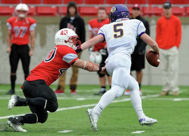 RPI's Mark Grimes, left, pressures Alfred's quarterback Tyler Johnson during their football game on Saturday, Sept. 13, 2014, Rensselaer Polytechnic Institute in Troy, N.Y. (Cindy Schultz / Times Union) Photo: Cindy Schultz / 00028529A
