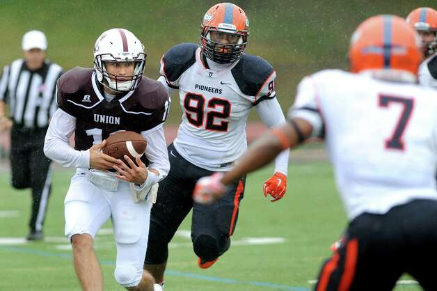 Union's quarterback Connor Eck, left, gains yards as Utica's Karl Simpson, center, defends during their football game on Saturday, Sept. 13, 2014, at Union College in Schenectady, N.Y. (Cindy Schultz / Times Union) Photo: Cindy Schultz / 00028530A