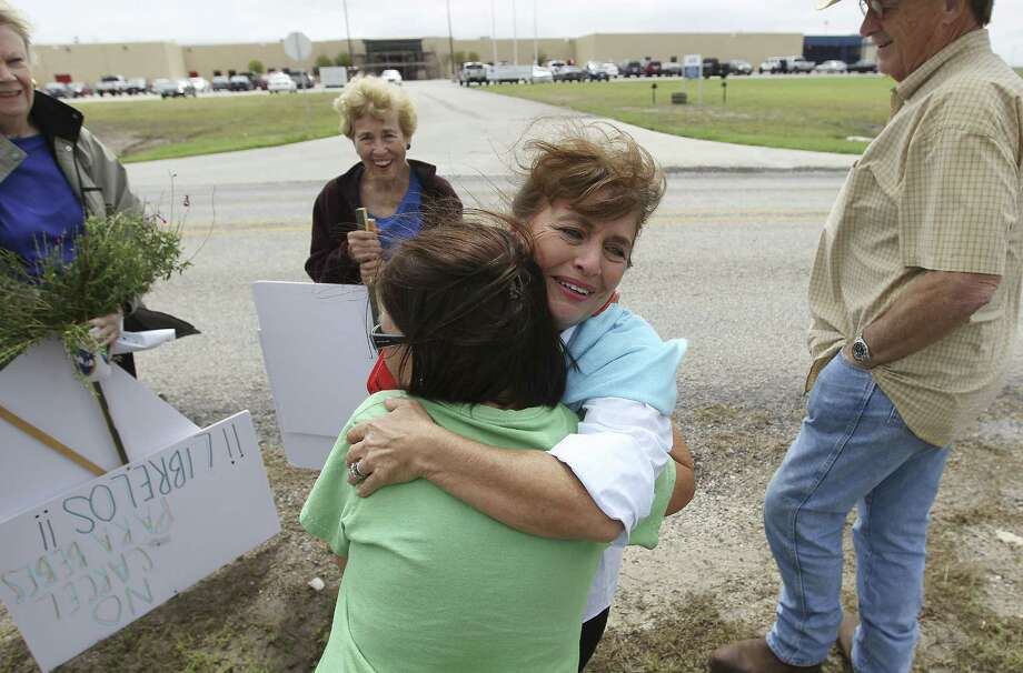 Susan Mitchell (center) hugs Karnes City resident Melinda Stulting during a rally in support of a Salvadoran immigrant family whose members said they fled to the U.S. in fear of their lives. Photo: Photos By Kin Man Hui / San Antonio Express-News / ©2014 San Antonio Express-News