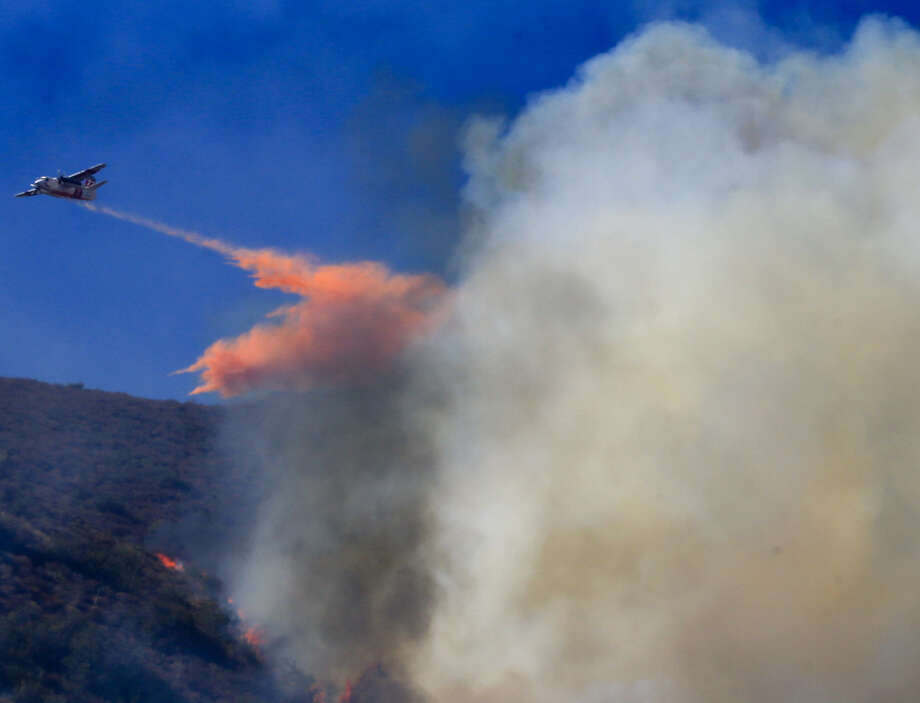 An airplane emerges from a cloud of smoke after dropping fire retardant on a blaze near South California's Cleveland National Forest. Photo: Mark Boster / Los Angeles Times / Los Angeles Times