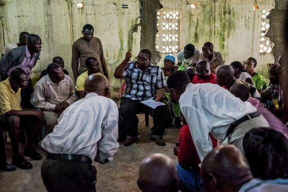 Dr. Mosoka Fallah, center, an epidemiologist and immunologist who grew up in Monrovia, talks with residents of New Kru Town, a district in the Liberian city about the Ebola virus. He has been crisscrossing the capital in an effort to win the cooperation of residents who are deeply distrustful of the government.