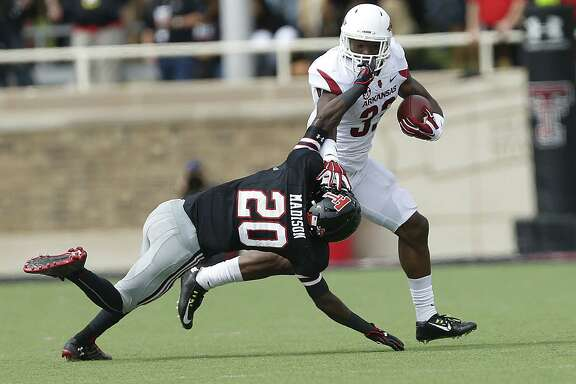 Arkansas' Korliss Marshall works past Texas Tech's Tevin Madison during an NCAA college football game Saturday, Sept. 13, 2014, in Lubbock, Texas. (AP Photo/The Avalanche-Journal, Tori Eichberger) ALL LOCAL TELEVISION OUT