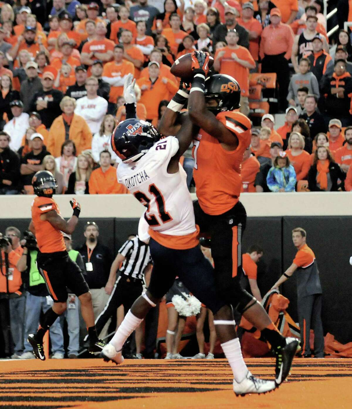 Oklahoma State wide receiver Brandon Sheperd, right, catches a touchdown despite the defensive efforts of UTSA cornerback Bennett Okotcha, during the first half of an NCAA college football game in Stillwater, Okla. Saturday, Sept. 13, 2014.