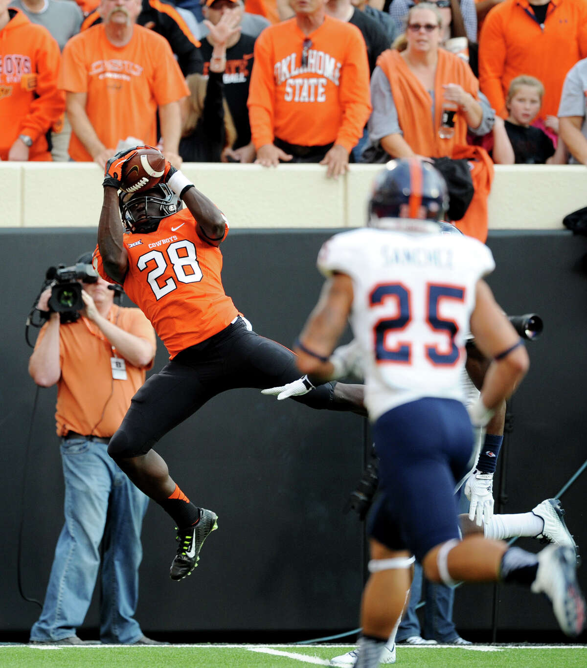 UTSA safety Mauricio Sanchez (25) races toward Oklahoma State wide receiver James Washington (28) as he catches a touchdown pass from quarterback Daxx Garman during the first half of an NCAA college football game in Stillwater, Okla. Saturday, Sept. 13, 2014. Oklahoma State defeated UTSA 37-13.