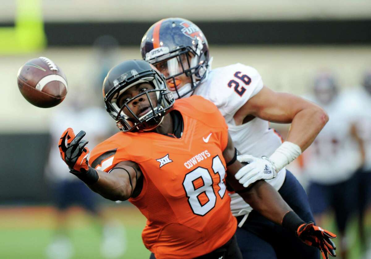 Texas-San Antonio cornerback Trevor Baker (26) holds onto Oklahoma State wide receiver Jhahuan Seales (81) as he stretches out for a missed pass during the first half of an NCAA college football game in Stillwater, Okla. Saturday, Sept. 13, 2014.