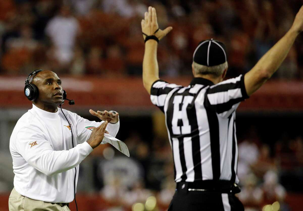 Texas coach Charlie Strong calls for a timeout during the first half of an NCAA college football game against UCLA, Saturday, Sept. 13, 2014, in Arlington, Texas.