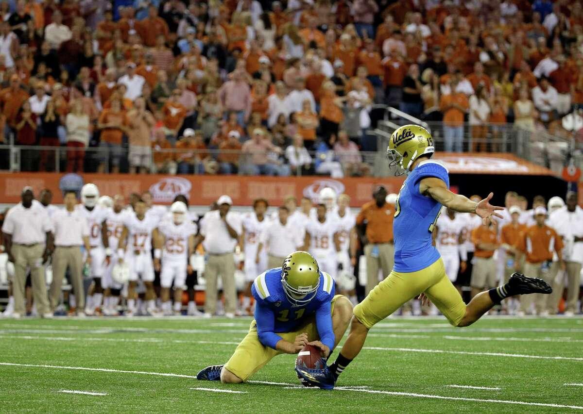 As UCLA quarterback Jerry Neuheisel holds, Ka'imi Fairbairn kicks a field goal against Texas during the second half of an NCAA college football game, Saturday, Sept. 13, 2014, in Arlington, Texas.