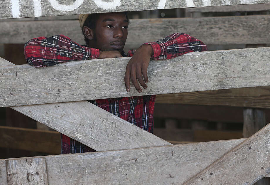 Worker DeAundre Walker, 19, takes a break during the weekly auction at the Karnes County Livestock Exchange in Kenedy. Photo: Jerry Lara / San Antonio Express-News / @San Antonio Express-News