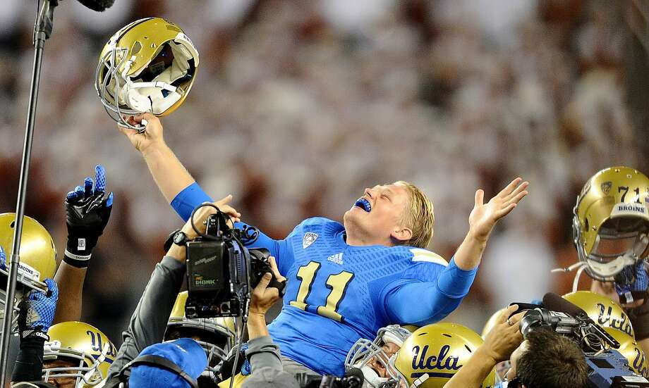 UCLA quarterback Jerry Neuheisel is lifted into the air by teammates after defeating Texas, 20-17, at AT&T Stadium in Arlington, Texas, on Saturday, Sept. 13, 2014. UCLA won, 20-17. (Wally Skalij/Los Angeles Times/MCT) Photo: Wally Skalij, McClatchy-Tribune News Service
