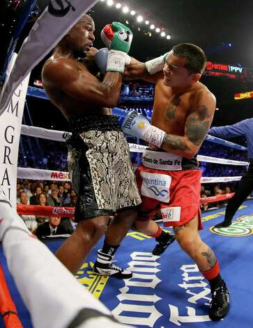 LAS VEGAS, NV - SEPTEMBER 13:  (L-R) Floyd Mayweather Jr. and Marcos Maidana exchange blows during their WBC/WBA welterweight title fight at the MGM Grand Garden Arena on September 13, 2014 in Las Vegas, Nevada.  (Photo by Al Bello/Getty Images) ORG XMIT: 500939137 Photo: Al Bello / 2014 Getty Images