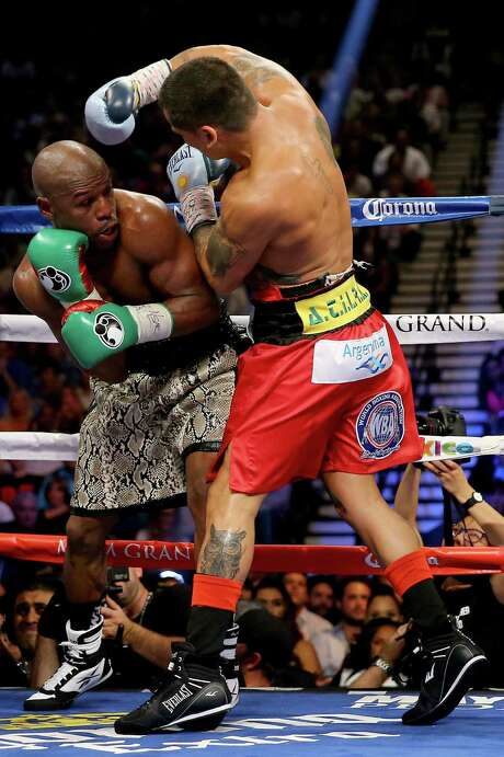 Floyd Mayweather Jr. tries to duck under a punch by Marcos Maidana at the MGM Grand in Las Vegas. Photo: Al Bello / Getty Images / 2014 Getty Images