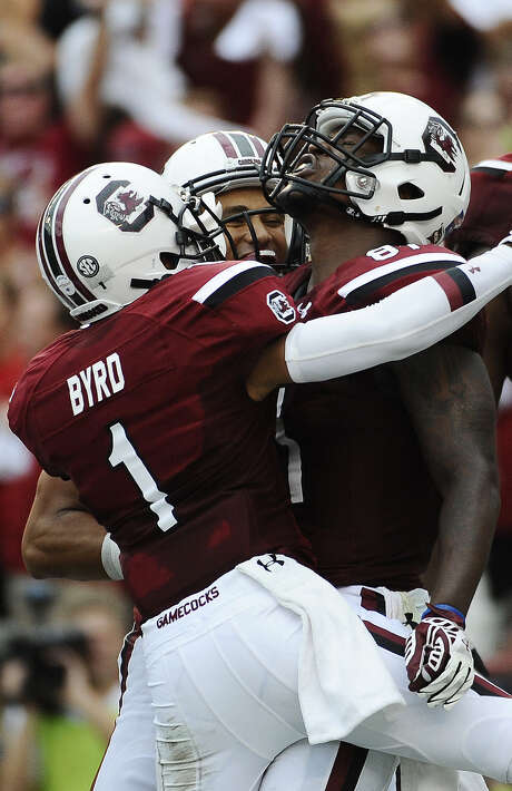Rory Anderson (right) celebrates with K.J. Brent (back) and Damiere Byrd during South Carolina's win. Photo: Rainier Ehrhardt / Associated Press / FR155191 AP