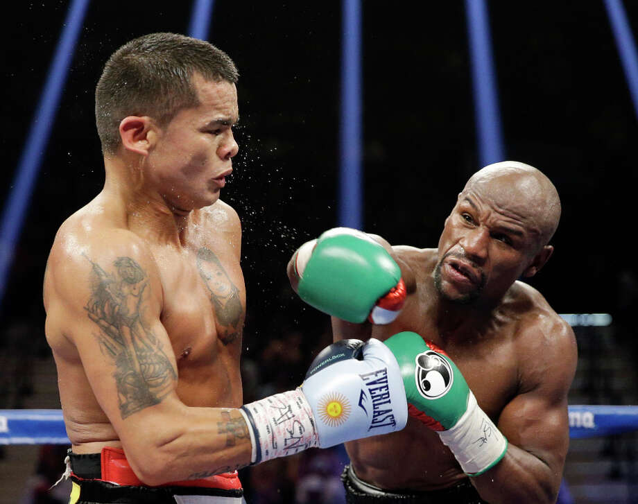 Floyd Mayweather (right), throws a straight right en route to winning a unanimous decision over Marcos Maidana in the welterollows through on a punch at Marcos Maidana during their title boxing match Saturday, Sept. 13, 2014, in Las Vegas. (AP Photo/John Locher) Photo: John Locher, STF / Associated Press / AP